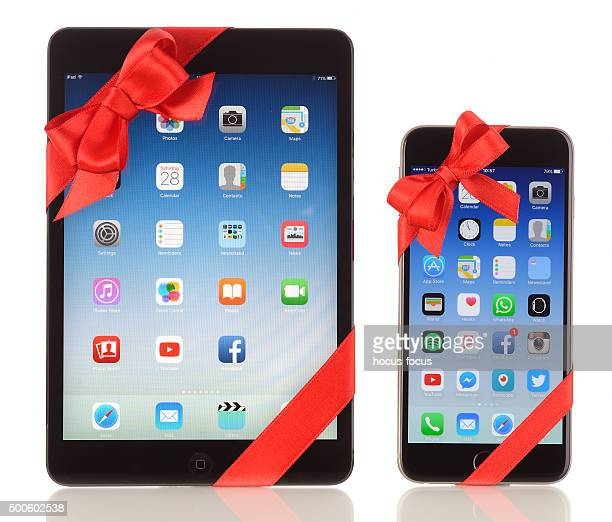 ipad mini and iphone 6 plus with red ribbon - gift icon stock photos and pictures