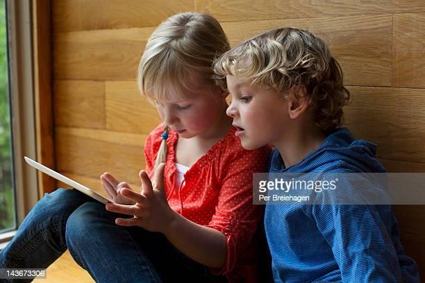 CHILDREN ENJOYING LOOKING AT AN iPAD
