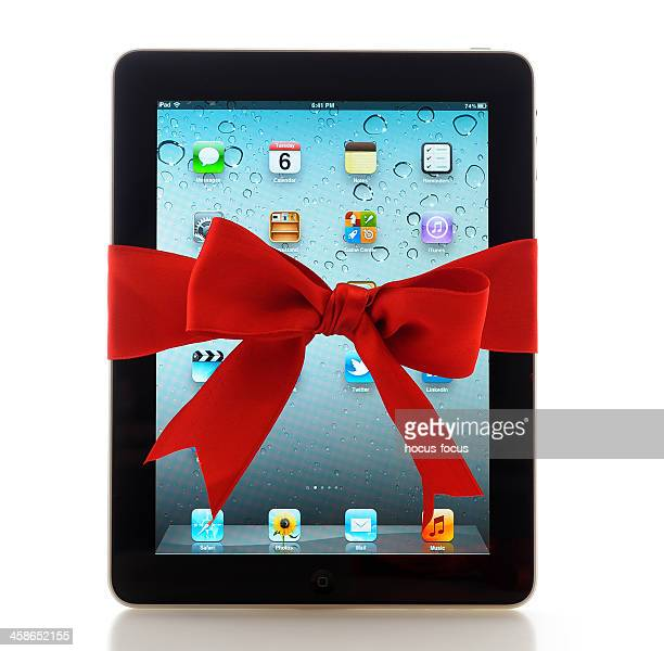 ipad with red ribbon - gift icon stock photos and pictures