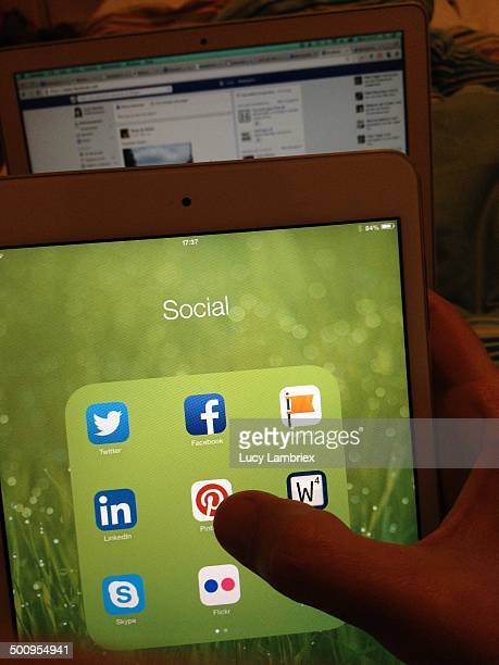 iPad with social media apps and laptop on Facebook