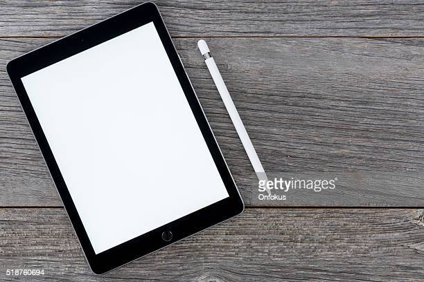 iPadPro (9.7 inch) SpaceGrey Isolated on Wood With Apple Pencil