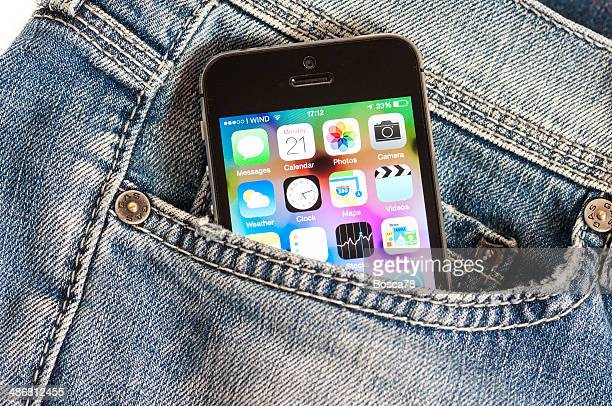 iphone 5s exiting from a denim trousers pocket - pocket stock photos and pictures