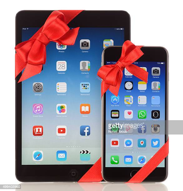 iphone 6 plus and ipad mini with red ribbon - gift icon stock photos and pictures