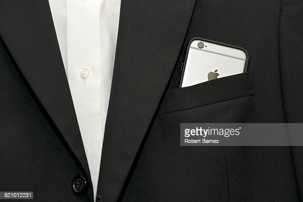A iPhone 6 sticking out of the front pocket of a Black suit jacket