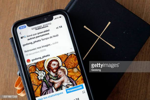 Iphone on a bible showing the explore page of the Instagram app with catholic images. France.