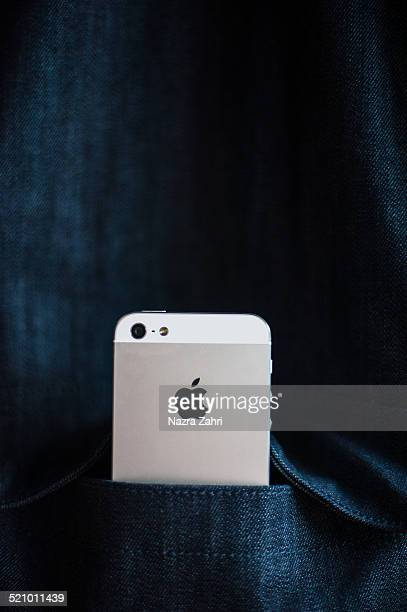 iPhone sticking out of denim jacket pocket