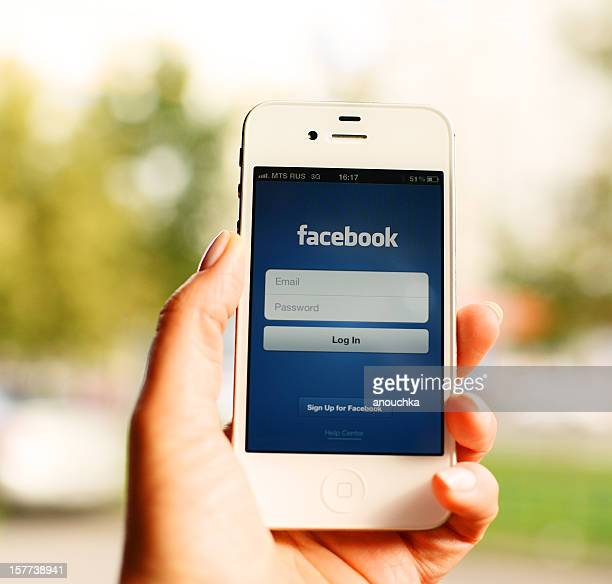 iPhone with Facebook main screen in woman hand