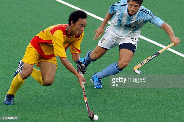 China's Feng Hui Lu controls the ball as Argentina's Gomas Argento gives chase during the third day of the 16th Sultan Azlan Shah hockey tournament...