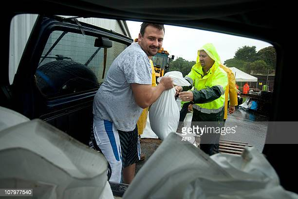 Ipswich resident Warwick Roberts loads his car with free sand bags from the Ipswich State Emergency Service amid heavy flooding in the area on...