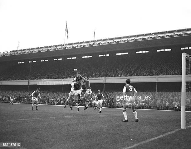 Ipswich Town goalkeeper Roy Bailey punches the ball clear of Arsenal's Geoff Strong and Ipswich Town teammates George Dougan and Andy Nelson