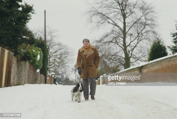 Ipswich Town manager Bobby Robson pictured walking his dog through the snow circa February 1980.