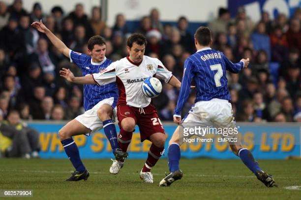 Ipswich Town's Alex Bruce and Owen Garvan tackle Burnley's Robbie Blake