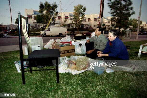 Iran Ashtari and his wife Emani eat dinner among their belongings in front of their quakedamaged apartment on January 17 1994 The earthquake which...
