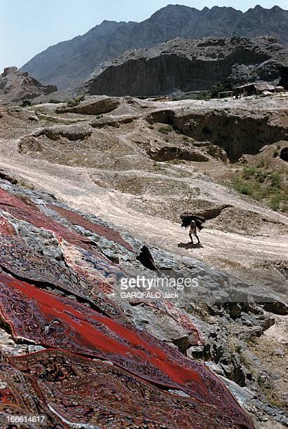 Iran En Iran des tapis étalés sur des rochers en premierplan un homme transporte des tapis enroulés sur son épaule sur une route de montagne...