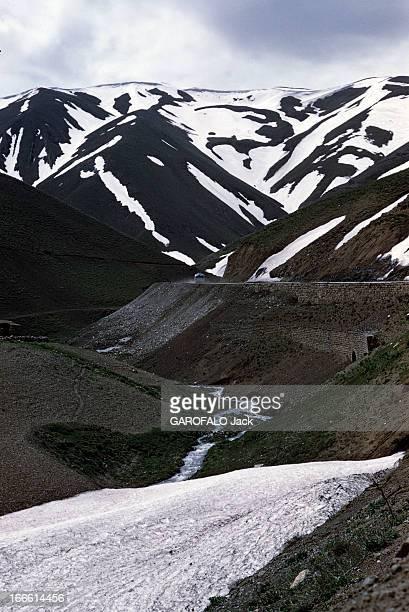 Iran En Iran en arrièreplan un autocar roule sur une route de montagne devant des sommets enneigés