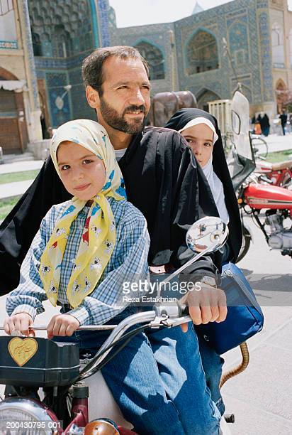 Iran, Isfahan, family riding motorbike outside Imam's Mosque