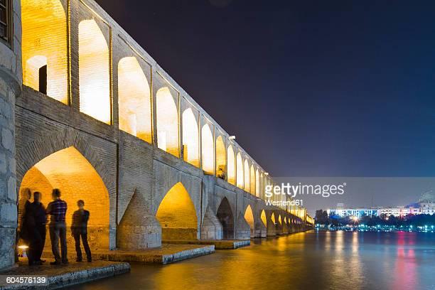 iran, isfahan, lighted arch bridge siosepol in the evening - isfahan stock-fotos und bilder