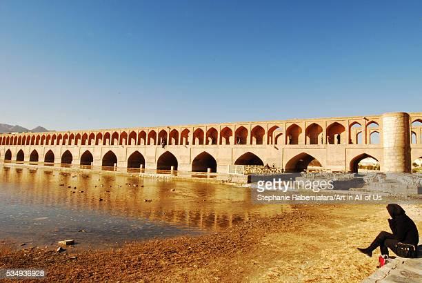 Iran, Isfahan, veiled woman sitting by Allah-Verdi Khan Bridge at low tide