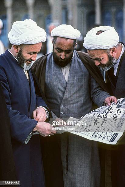 CONTENT] Iran three shia clerics with white turban read a newspaper in the big mosque of Qom the holy city of islam shia