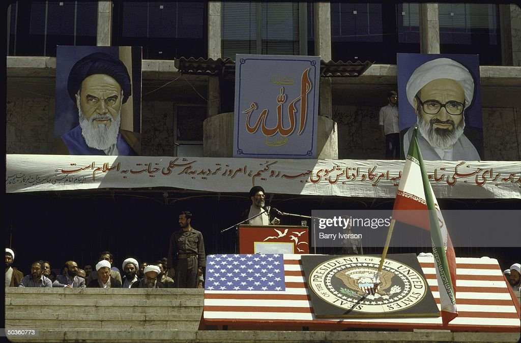 Iranain President Seyyed Ali Khamenei speaking at anti-US demonstration after the USS Vincennes shot down and Iranian Airbus. Also shows the US flag and presidential seal stabbed with an Iranian flag pole and banners depicting Ayatollah Khomeini andHossein Ali Montazeri.