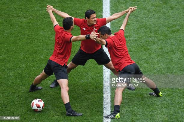Irani referee Alireza Faghani warms up with his assistants ahead of the Russia 2018 World Cup playoff for third place football match between Belgium...