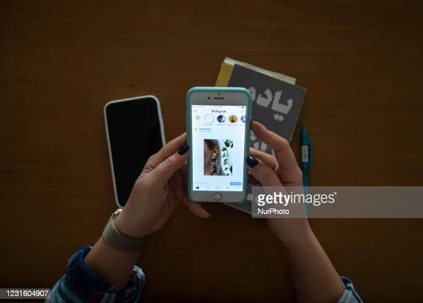 Iranian 35-year-old female and owner of the Hastijewelry brand, Hasti Hezaveh, checks her Instagram page on her smartphone while sitting in her...