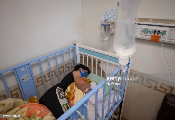 Iranian 65yearold boy Mehran who is infected by the new coronavirus disease wearing a protective face mask as he lies on a hospital bed in the...