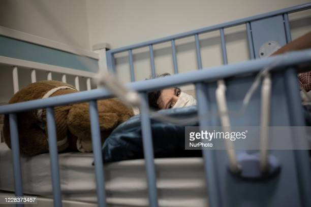 Iranian 7yearold boy Mohammad Amin who is infected by the new coronavirus disease wearing a protective face mask as he lies on a hospital bed in the...