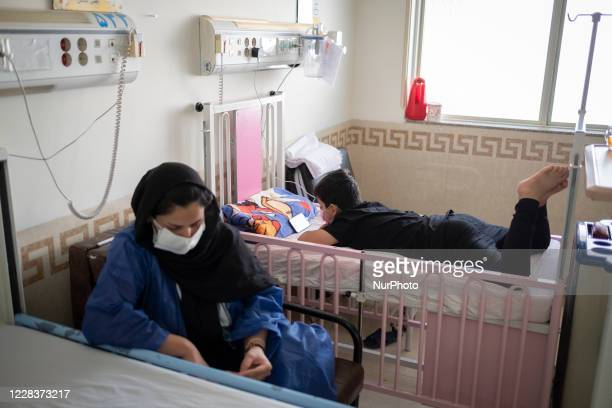 Iranian 85yearold boy Mahan who is infected by the new coronavirus disease uses his smartphone as his mother Sara wearing a protective face mask sits...