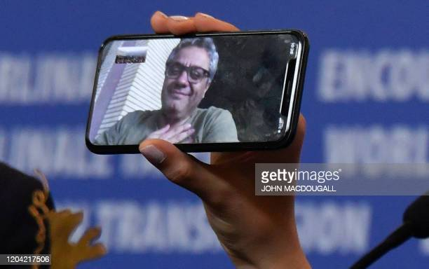 TOPSHOT Iranian actress Baran Rasoulof holds a phone displaying Iranian director Mohammad Rasoulof who was awarded the Golden Bear for Best Film...