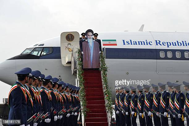 Iranian air force soldiers carry a cardboard cut out of late founder of Islamic Republic Ayatollah Ruhollah Khomeini down the stairs of a passenger...