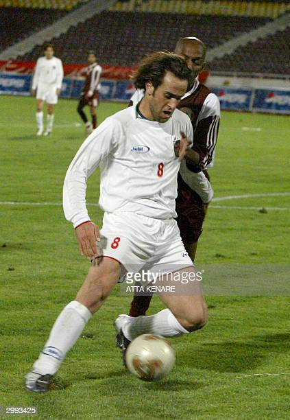 Iranian Ali Karimi fights for the ball against Qatari Yousef Adam Mahmoud during their World Cup Asian qualifiers match in Tehran 18 February 2004...
