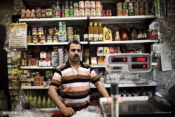 Iranian Alireza Vafaei poses in his grocery in Mokhtari neighbourhood in southern Tehran on April 22 2014 Iran's President Hassan Rouhani was elected...