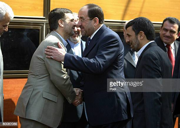 Iranian ambassador to Iraq Hassan Kazemi Qomi embraces Iraqi Prime Minister Nuri alMaliki as Iranian President Mahmoud Ahmadinejad looks on at...