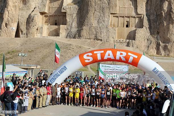 Iranian and foreign runners wait on the starting line of the first International Marathon in Iran in front of the ancient Achaemenid necropolis of...