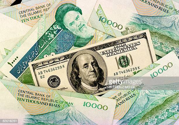 Iranian and US bills are displayed 12 November in Tehran. An Iranian finance ministry official blamed illegal imports of goods for the dramatic fall...