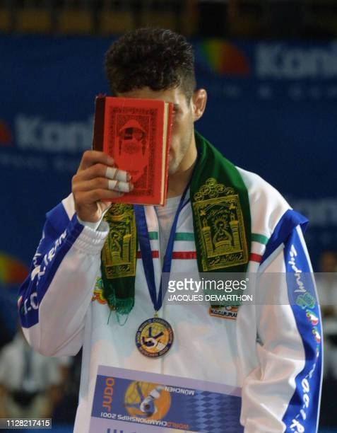 Iranian Arash Miresmaeili kisses the Muslim holy book the Koran after winning the gold medal in the under66kg category in the World Judo Championship...