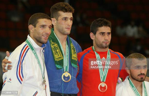 Iranian Arash Miresmaili winner of the men's under 66 kg class poses with second place winner Larbi Benboudaoud of France and third place winners...