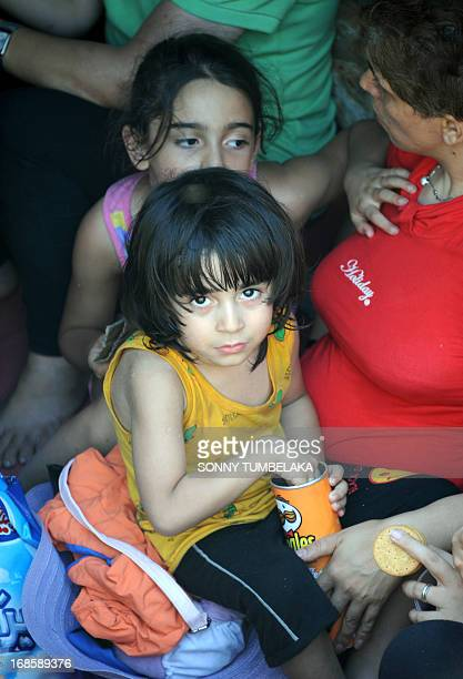 Iranian asylum seekers sit on a boat at Benoa port in Denpasar on Indonesia's island of Bali on May 12 2013 Indonesia marine police arrested 95...