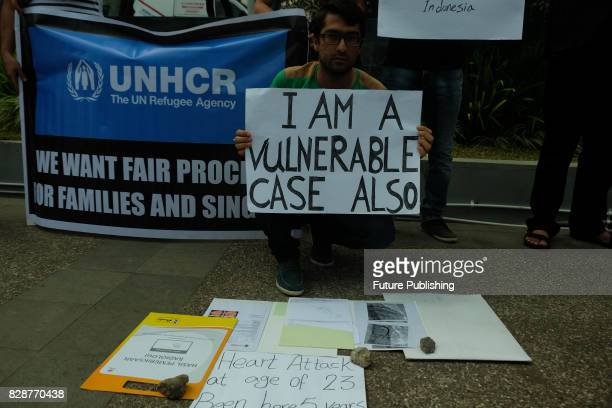 Iranian asylumseeker holds a placard during a rally in front of the UN High Commissioner for Refugees office as they demand to be transferred to a...