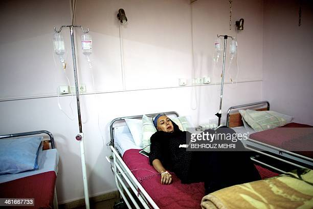 Iranian breast cancer patient Farvah reads a book as she receives her chemotherapy treatment at a clinic in Tehran on September 9 2013 According to...