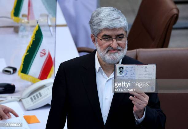 Iranian candidate Ali Motahari waves his identification documents as he arrives at the Interior Ministry headquarters in the capital Tehran on May...