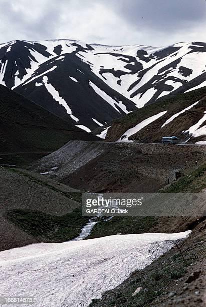 Iranian Caviar Of The Caspian Sea En Iran un autocar roule sur une route de montagne devant des sommets enneigés
