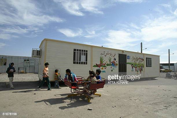 Iranian children play in front of a newly built house 05 November 2004 in the southeastern devastated city of Bam where a powerful earthquake killed...