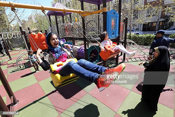 Iranian children play on a swing at a park in northern Tehran on April 2 2015 as they celebrate 'Sizdah Bedar' on the 13th day of Noruz which people...