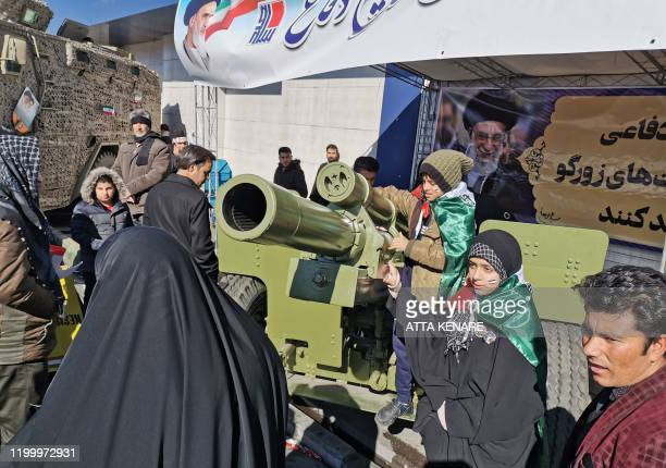 Iranian children pose with howitzer artillery gun during commemorations marking 41 years since the Islamic Revolution in the capital Tehran on...
