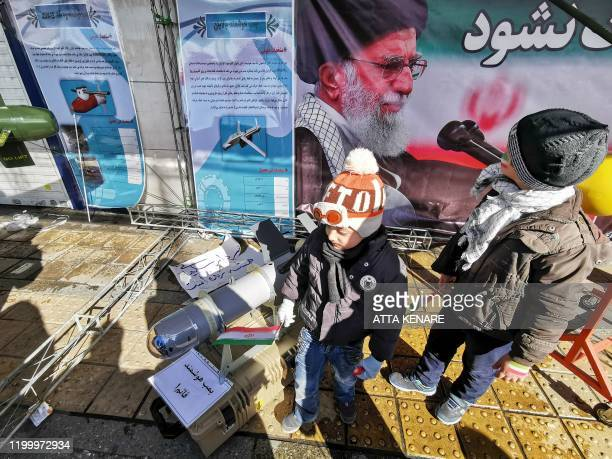 Iranian children pose with replica military equipment during commemorations marking 41 years since the Islamic Revolution in the capital Tehran on...