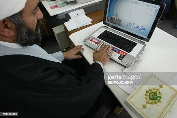 Iranian clergyman Nematollah Daneshmand webmaster for saneeiorg the site of Grand Ayatollah Yusuf Saanei works on his laptop with a copy of the Koran...