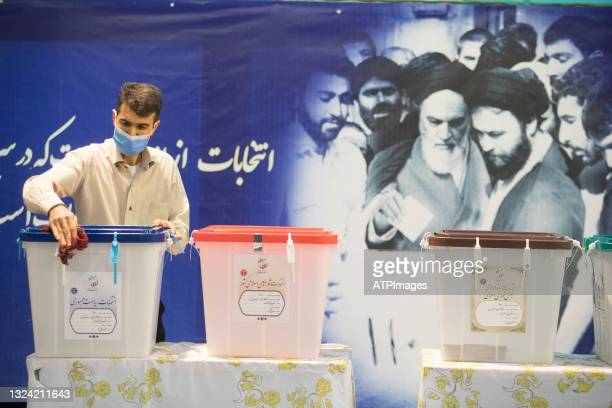 Iranian cleric and people wait a polling station to vote for presidential election, on June 18, 2021 in Tehran, Iran. The country's incumbent...
