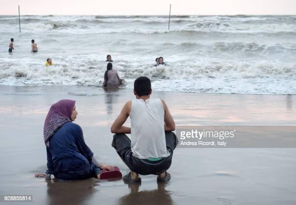 iranian couple at seaside, caspian sea, iran - muslim woman beach stock photos and pictures